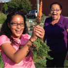 Photo of girl proudly showing a carrot grown in community garden
