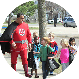 Photo of Jonathan Palmer dressed as a superhero walking with a group of children
